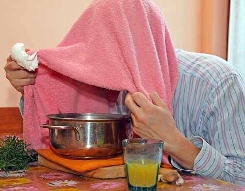 man with towel breathe balsam vapors to treat colds and the flu and a glass of orange juice